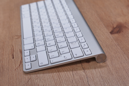 Modern aluminum keyboard on the wooden table in the office Stock Photo