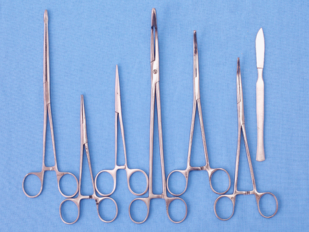 surgical instruments and tools including scalpels, forceps and tweezers arranged on a table for a surgery