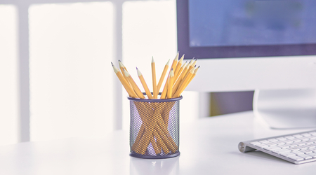 Graphite pencils in a metal grid-container on the office table. Concept.