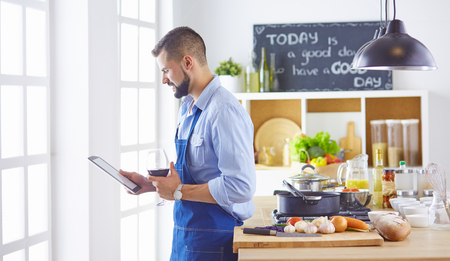 cook with a tablet in hand and studying the recipe Stock Photo