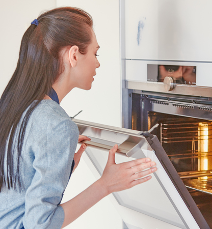 Beautiful woman in the kitchen, waiting with the front of the oven.