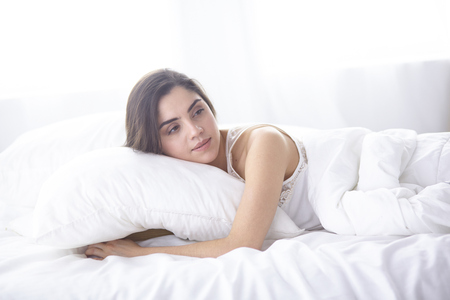 beautiful young woman basking in bed in the morning. Beautiful Banco de Imagens