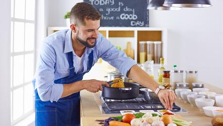 Chef sonriente y confiado de pie en la cocina grande