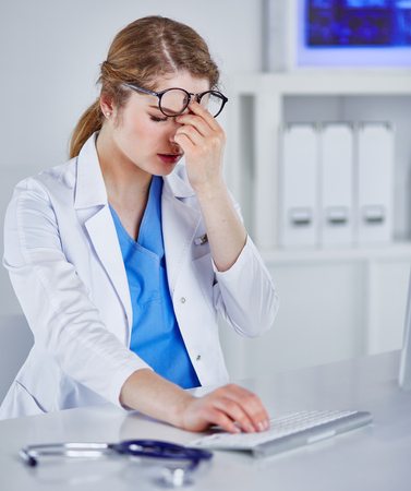 Young female doctor tired after working with computer Banque d'images