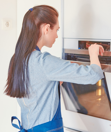 Beautiful woman in the kitchen, waiting with the front of the o Stock Photo