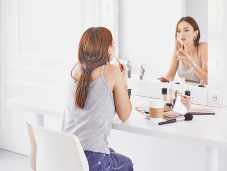 Amazing young woman doing her makeup in front of mirror. Portra