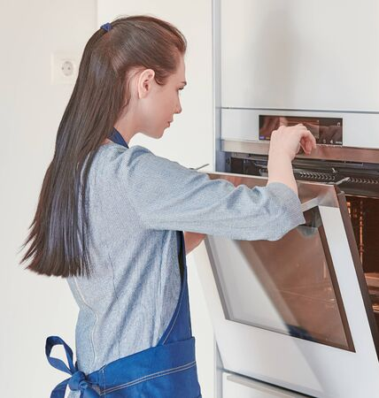 Beautiful woman in the kitchen, waiting with the front of the oven Фото со стока