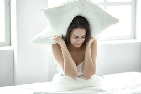 Annoyed young woman covering ears with pillow, blocking sound, suffering from noise, lying in bed, problem with sleep