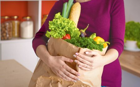 Healthy positive happy woman holding a paper shopping bag full
