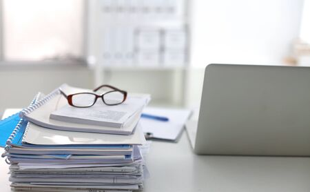 Laptop mit Stapel von Ordnern auf Tabelle auf weißem Hintergrund