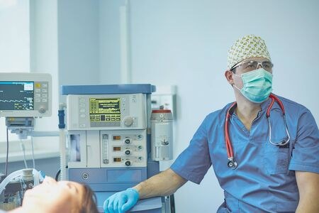 Several doctors surrounding patient on operation table during t