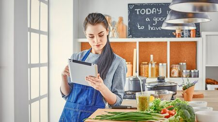 Happy woman looking recipe tablet kitchen reading cooking