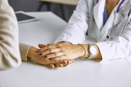 Woman doctor calms patient and holds hand. Фото со стока