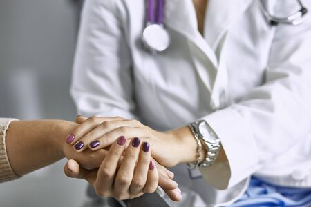 Woman doctor calms patient and holds hand Фото со стока