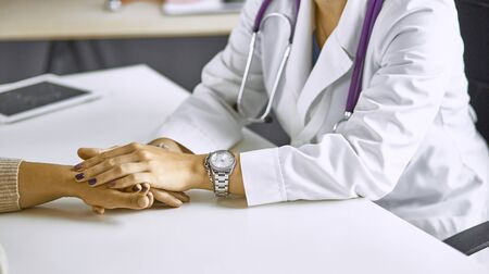 Woman doctor calms patient and holds hand Stock fotó