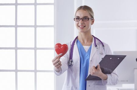 Doctor with stethoscope holding heart, isolated on white backgr