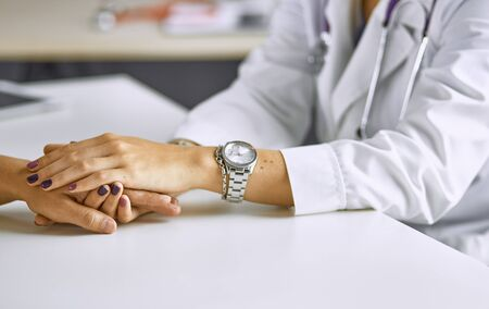 Woman doctor calms patient and holds hand Stok Fotoğraf