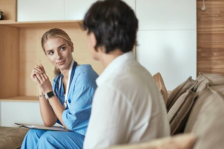 Friendly smiling doctor and patient sitting on the couch. Very good news and high level medical care concept. Stok Fotoğraf