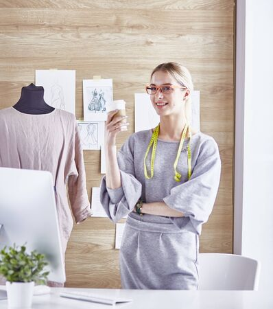 Attractive fashion designer working in office, leaning on desk, drawing