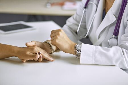 Woman doctor calms patient and holds hand Standard-Bild - 131363318