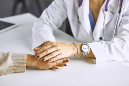 Woman doctor calms patient and holds hand Standard-Bild - 131363812