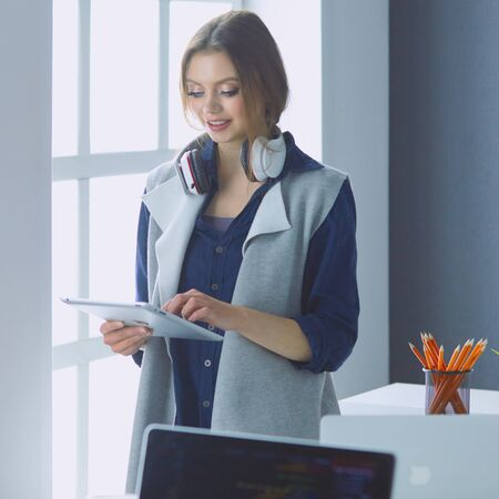 Focused attentive woman in headphones sits at desk with laptop,