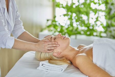 Beautiful woman with closed eyes getting a massage in the spa salon.