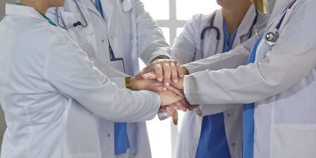 Team of medical workers holding hands together indoors, above view. Unity concept. Stock Photo