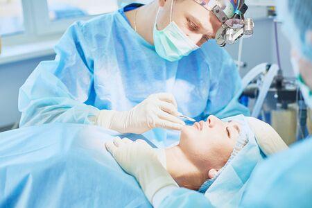 Verschillende artsen omringen de patiënt op de operatietafel tijdens hun werk. Teamchirurgen aan het werk in de operatiekamer. Stockfoto
