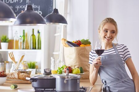 Beautiful woman in kitchen is drinking red wine