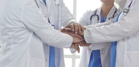 Team of medical workers holding hands together indoors, above view. Unity concept Stock Photo