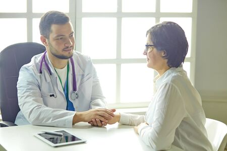 Young doctor talking to a patient in the office