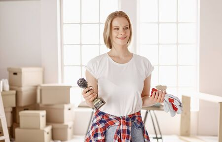 A young girl dressed for repair stands and holds a screwdriver in her hand. Tools for girls and men