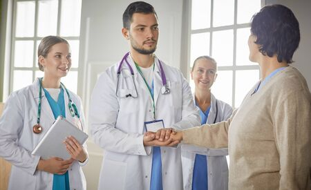 Patient with a group of doctors at the background Archivio Fotografico