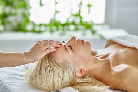 Belle femme aux yeux fermés se faisant masser dans le salon spa. Banque d'images
