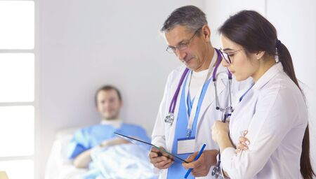Doctor checking heart beat of patient in bed with stethoscope Imagens