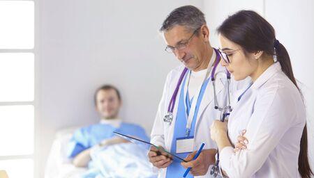 Doctor revisando los latidos del corazón del paciente en la cama con estetoscopio Foto de archivo