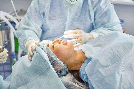 Several doctors surrounding patient on operation table during their work. Team surgeons at work in operating room. Stockfoto