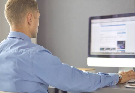 Young businessman working in office, sitting at desk, looking at laptop computer screen, smiling.