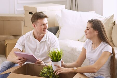 Portrait of happy couple looking at laptop computer together sitting in new house, surrounded with boxes