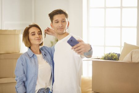 Happy smiling young couple showing a pair of keys of their new house Banque d'images