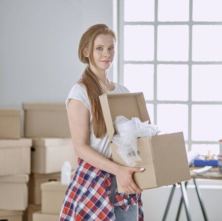A beautiful single young woman unpacking boxes and moving into a new home