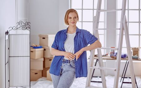 Beautiful young woman on a white wooden stepladder. Ready to repair the room. Women housework concept