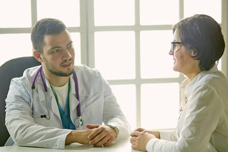 Young doctor talking to a patient in the office Banque d'images