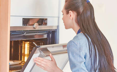 Beautiful woman in the kitchen, waiting with the front of the oven