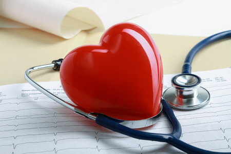 Red heart and a stethoscope on cardiagram ,lying on the desk photo