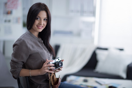proffessional: Woman is a proffessional photographer with camera in office