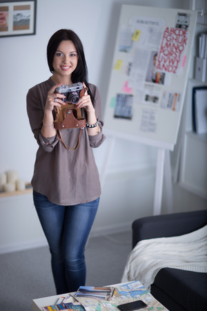 Woman is a proffessional photographer with camera in office photo