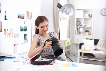 Young woman photographer processing pictures sitting on the desk photo