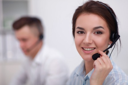 customer service representative: Businesswoman with headset smiling at camera in call center